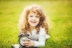 Girl lying on the green grass and holding alarm clock. Royalty Free Stock Photography