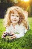 Girl lying on the green grass and holding alarm clock. Royalty Free Stock Image
