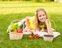 Girl lying on green grass with vegetables and berry Royalty Free Stock Photography