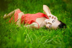 Girl lying in green summer bright grass. Fashion portrait of beautiful sexy female brunette girl model lying in green summer bright grass in the park with makeup Royalty Free Stock Images