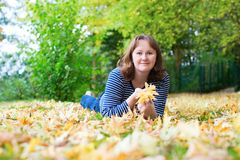 Girl lying on the ground covered with fall leaves Royalty Free Stock Image