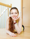 Girl lying on hardwood floor Stock Images