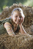 Girl (9-11) lying on hay, smiling, side view, portrait Royalty Free Stock Photo