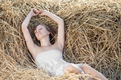Girl lying on a hayloft Stock Photos
