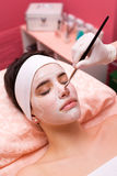 Girl lying in health and beauty spa while facial mask is applied Royalty Free Stock Photography