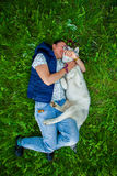 Girl lying with her puppy on green grass Royalty Free Stock Photo