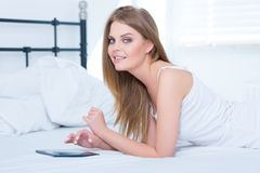 Girl lying on her stomach in bed Royalty Free Stock Photos