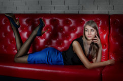 Girl lying on her stomach on a red leather couch in the dim light, one hand propped his head, feet raised and apart. she is. Smiling and wearing a black blouse stock photo
