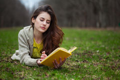 Girl Lying In A Grass And Reading Book Royalty Free Stock Photography