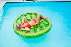 Girl lying on inflatable in swimming pool. Overhead view of blond girl in red bikini sunbathing on round inflatable in swimming pool royalty free stock photography
