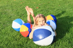 Girl lying among inflating balls Royalty Free Stock Image