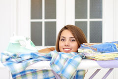 Girl lying on ironing board Royalty Free Stock Photos