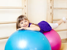 Girl lying on large gymnastic balls Royalty Free Stock Images