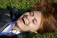 Girl lying on a lawn and laughing. The photograph of a girl lying on a lawn and laughing Royalty Free Stock Photography