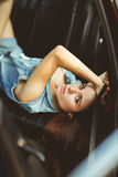 Girl lying on leather seat of car. tinted photo Royalty Free Stock Photography