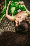 Girl lying on a log. In the woods in a green dress Royalty Free Stock Images