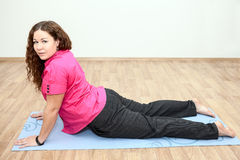 Girl lying on mat in one of the yoga positions Stock Photo