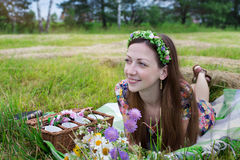 Girl lying on meadow. Freckled girl lying on plaid in meadow and looking away Stock Image