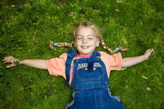 Girl lying on moss. A sweet little girl lying on moss with outstretched arms Stock Image