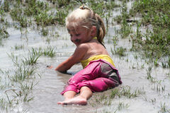 Girl lying in muddy water. Little girl playing in muddy water dirtying her clothes royalty free stock photo