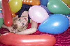 Girl Lying With Multicolored Balloons On Bed Royalty Free Stock Images