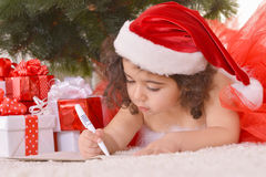 Girl lying near Christmas tree stock images