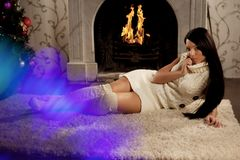 Girl lying near the fireplace Stock Photography