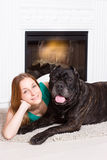 Girl lying near the fireplace with a dog Cane Corso Royalty Free Stock Photos
