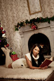 Girl lying near the fireplace and reads a book Stock Photography
