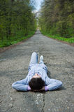 Girl Lying On The Mountain Road Royalty Free Stock Image