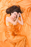 Girl lying on orange satin Stock Images
