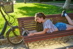 Girl lying on park bench playing with tablet royalty free stock photography