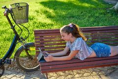 Girl lying on park bench playing with tablet stock image