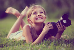Girl  lying in park with camera Royalty Free Stock Photos