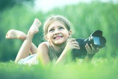 Girl  lying in park with camera Stock Photos