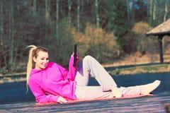 Girl lying in park using tablet. stock image
