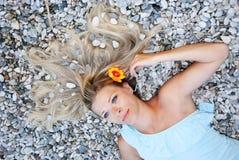 Girl on the pebbles near the sea Stock Photos