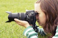 Girl lying with photo camera Stock Photos