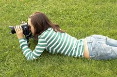 Girl lying with photo camera Stock Photos