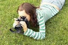 Girl lying with photo camera Royalty Free Stock Images