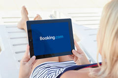 Girl lying by the pool and holding ipad with app Booking on the Stock Photography