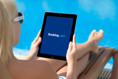Girl lying by the pool and holding ipad with Booking on the scre Stock Image