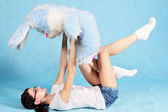 Girl lying in a pose holding a toy rabbit in her arms. Stock Photo