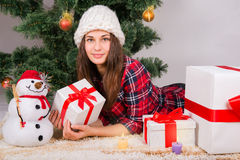 Girl lying between the presents under the Christmas tree. Pretty girl lying between the presents under the Christmas tree Royalty Free Stock Photography