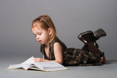 Girl lying and reading. Small beauty girl lying and reading interesting book stock images