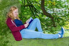 Girl lying reading book in green tree stock photos