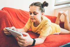 A girl is lying on a red sofa on the balcony with a tablet royalty free stock images