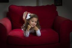 girl lying on red sofa royalty free stock image