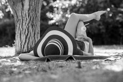 Girl lying relaxing in her back under a tree with a drink and br Royalty Free Stock Photo