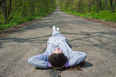 Girl lying on the road in the forest Royalty Free Stock Photography